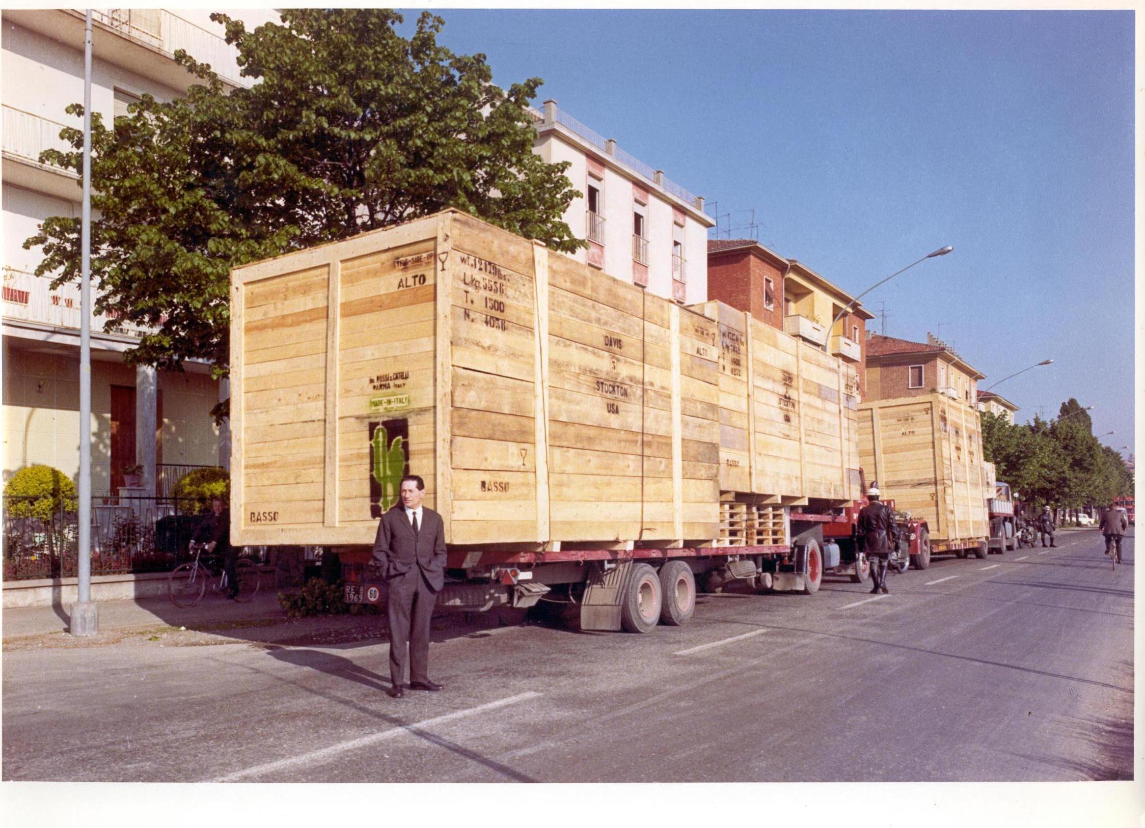 Camillo Catelli ripreso davanti ad un convoglio di macchinari in spedizione negli anni Ottanta del Novecento.